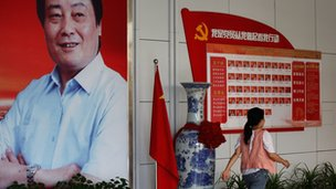 A employee walks past the boss Zong Qinghou's picture at Wahaha Group