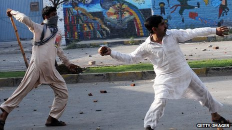 Pakistani Muslim demonstrators throw stones towards police during a protest against an anti-Islam film in Lahore on September 21, 2012