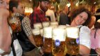 A waitress carries beer glasses in the Hofbraeuhaus tent