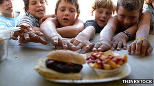Children reaching for a burger and chips