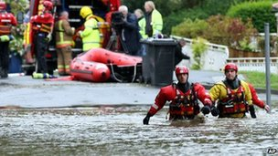 Rescue workers wade through flood water in Morpeth