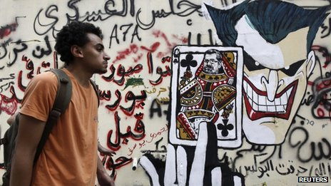 A man walks past a mural on Mohammed Mahmoud street showing Mohammed Mursi's head on a queen of clubs playing card