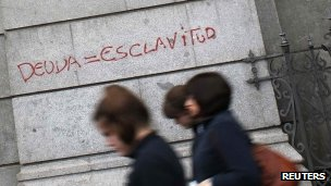 Passers-by outside Spain&#039;s central bank in Madrid