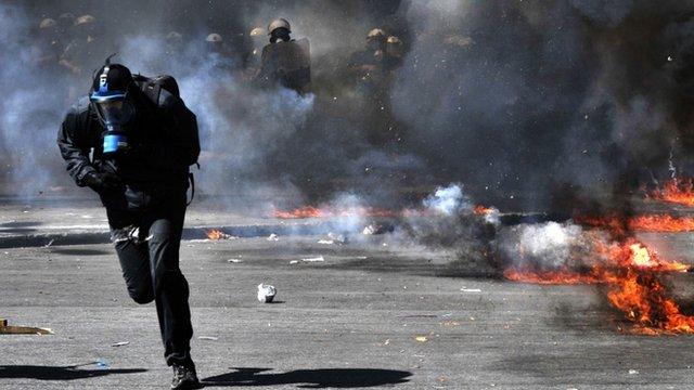 Protestor runs from riot police