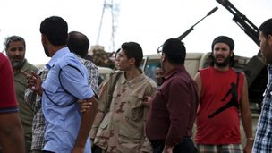 Members of the Rafallah Sahati Islamic Militia Brigades argue with a Libyan policemen