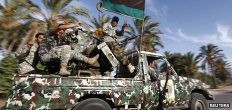 Libyan security forces head to a compound which had been taken over by an armed group in Tripoli 23 September 2012