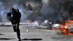 A protester runs from riot police during a general strike in Athens