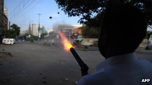 Policeman fires tear gas at demonstrators in Karachi on 21 September 2012