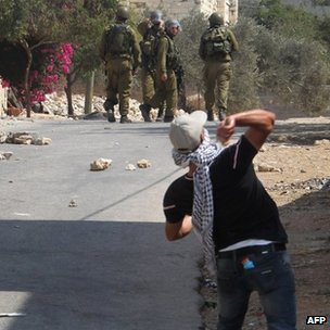 A Palestinian protester throws stones towards Israeli soldiers during a demonstration against the expropriation of Palestinian land by Israel in the village of Kfar Qaddum near Nablus