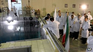 Iranian President Mahmoud Ahmadinejad, right, is escorted by technicians during a tour of Tehran's research reactor centre in northern Tehran in February 2012