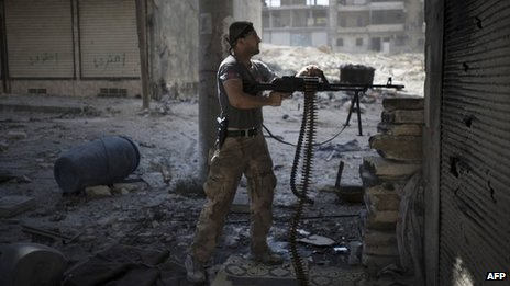 A rebel fighter fires a machine-gun at government forces in Aleppo (27 September 2012)