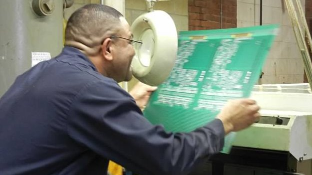 Employee inspects a circuit board at the Electropac factory
