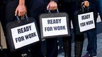 Students hold brief cases labelled 'ready to work'