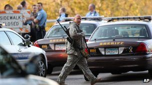 An officer walks through the area as police investigate a shooting at Accent Signage Systems on the north side of Minneapolis on 27 September 2012