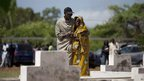 A man comforts a grieving woman at the Mbao cemetery in Senegal - Wednesday 26 September 2012