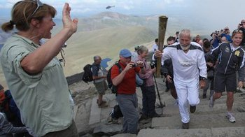 Sir Chris Bonington holds the Olympic torch as he approaches the summit of Mount Snowdon