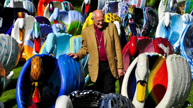 The Bishop of Bath and Wells, Peter Price, checks out the giant flock of around 60 brightly coloured swan sculptures in the grounds of the Bishops Palace, Wells.