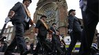 Orange Order members parade past St Patrick's Catholic church