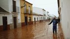 A man wades through flood waters in Bobadilla, near Malaga southern Spain.