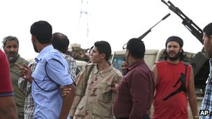 Members of the Rafallah Sahati Islamic Militia Brigades, argue with a Libyan policemen, second left, regarding a request for the militia to evacuate their base in Benghazi, Libya, Saturday, Sept. 22, 2012.