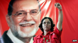 A supporter raises her fist in front of a portrait of the Farabundo Marti for National Liberation Front (FMLN) leader Schafik Handal, as she pays homage during a special ceremony at the National University in San Salvador 27 January 2006.