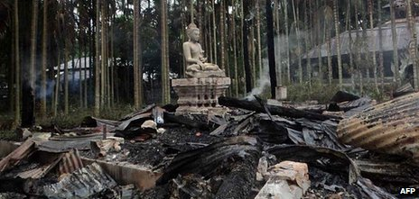 A statue of Buddha is left standing amidst the torched ruins of the Lal Ching Buddhist temple at Ramu on September 30