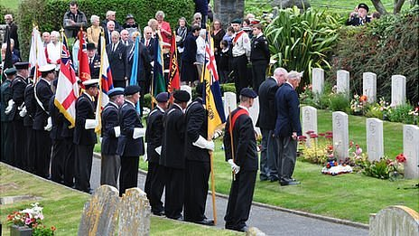 Wreaths laid on the graves of those lost in the sinking of HMS Charybdis and Limbourne in 1943 by survivors