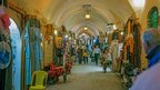 People walking through a hall with clothes hanging along the walls, Aleppo souk. Photo: Simon Jenkins.