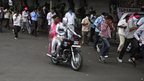 "Protestors run to escape police teargas as one of them dressed as Mahatma Gandhi rides a motorcycle during a protest demanding the creation of a new state named ""Telangana"" in Hyderabad, India, Sunday, Sept. 30, 2012"
