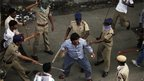 "Indian policemen baton-charge an activist, centre, who allegedly pelted stones at them during a protest demanding the creation of a new state named ""Telangana"" in Hyderabad, India, 30 September, 2012"