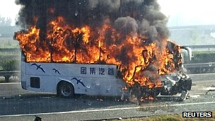 A tourist bus, seen through the window of a vehicle, catches fire after crashing with a truck on the Beijing-Tianjin-Tanggu Expressway in Tianjin, 01 Oct 2012