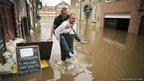 A man carries another man through floodwater
