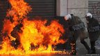 Riot policemen on fire after a petrol bomb thrown by protesters ignited during a nationwide general strike in Athens