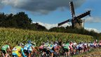 A peloton rides past a windmill in Netherlands