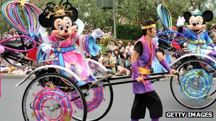 Minnie Mouse being pulled in a cart at a theme park