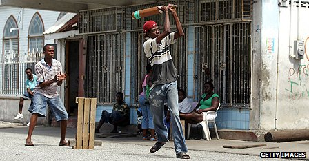 Youths playing a street cricket match in the capital of Guyana, Georgetown, in May 2010