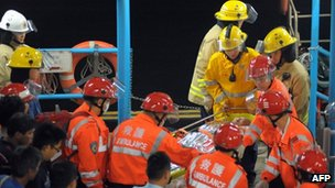 Rescue workers carry a victim ashore after a ferry collided with a tug boat off Hong Kong on 1 October, 2012