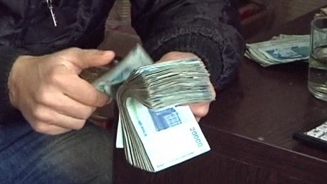 Man counting wad of rial notes