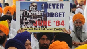 An activist from a radical Sikh organization holds a poster showing the 1984 damage of the Sri Akal Takht at the Golden Temple in Amritsar on June 6, 2009.