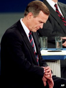 George H W Bush looks at his watch during a 1992 presidential debate