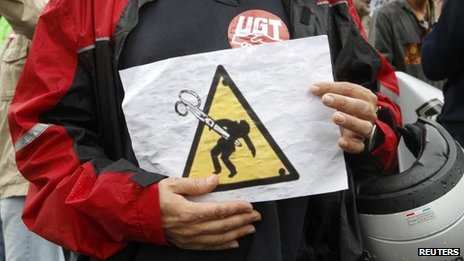 A public-sector worker holds a sign protesting against austerity cuts during a protest against Spain&#039;s 2013 cost-cutting budget, in Barcelona on 28 September 2012 
