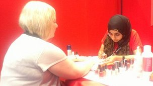 A woman gets her nails painted at conference