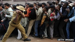 Indian policeman attempts to control a queue using a bamboo stick ( February 2011)