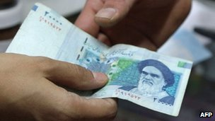 A rial note changing hands
