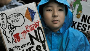 A boy holds a banner denouncing nuclear