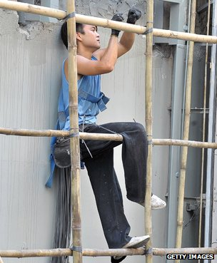 Construction worker erecting bamboo scaffolding