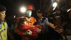 A young survivor is carried by a rescuer in Hong Kong, 2 October 2012