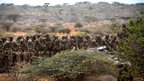 Kenyan soldiers serving with the African Union Mission in Somalia (Amisom) sit on a flatbed truck as a convoy makes its way between the port and the airport in Kismayo, southern Somalia, in this photo released by the African Union-United Nations Information Support Team 