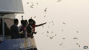 Relatives of the victims throw paper money on board a boat as they pay tribute to the 38 people killed in the 1 Oct boat collision near Lamma Island in Hong Kong, 02 Oct 2012