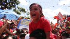 A child reacts during a campaign rally by Venezuela's President